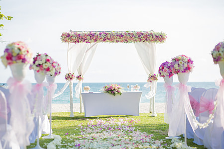 white, pink, and yellow floral wedding arch during daytime