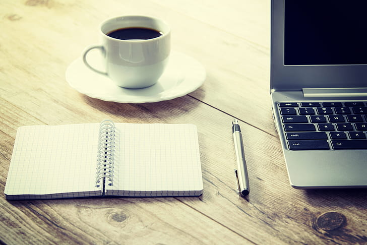 Royalty-Free photo: White cup and saucer beside gray laptop ...