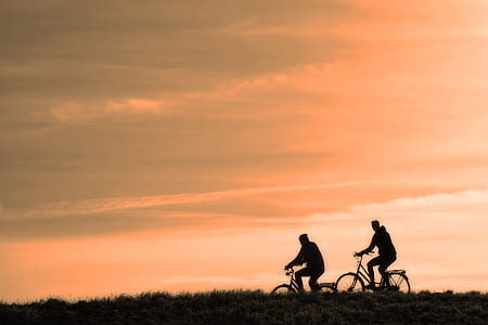 two silhouette of man riding bicycle during golden hour time