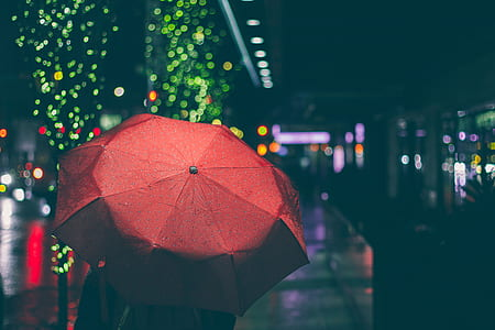 person using red umbrella with bookeh lights photography