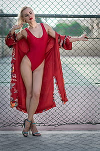 woman wearing red one-piece swimwear with red floral robe near gray metal fence