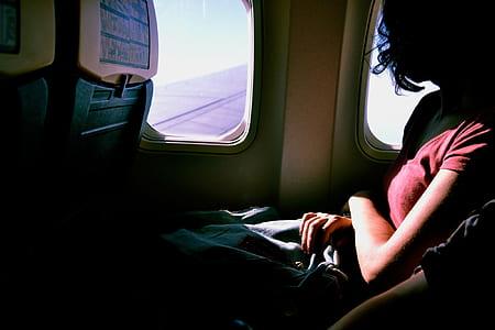 woman wearing red t-shirt inside airplane beside window