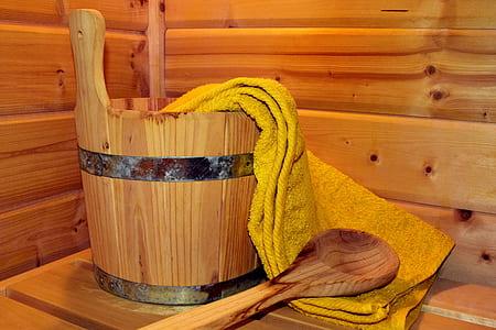 brown wooden ladle beside bucket