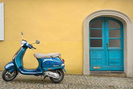 blue motor scooter beside yellow concrete house