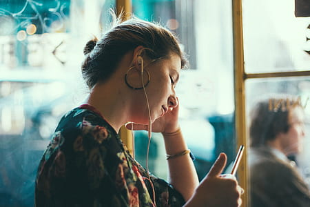 selective focus photography of woman in black and multicolored floral top with white earbuds