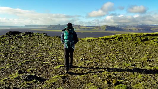 Person in Green Coat Walking on Mountain