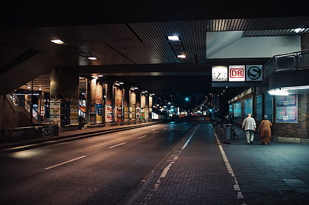 two person walking beside the road during nighttime