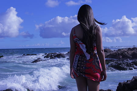 woman in red mini dress standing near sea during daytime