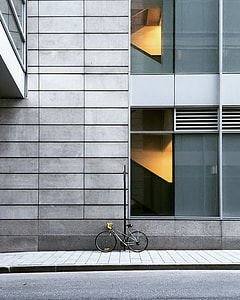 grey bicycle parked near grey concrete building during daytime
