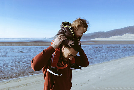 man carrying toddler on her back near body of water