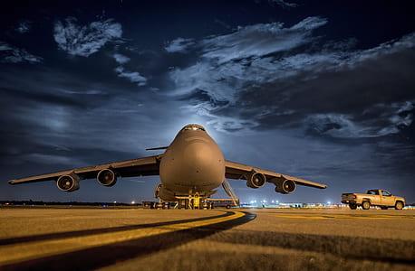 photo of airplane near pickup truck under blue sky