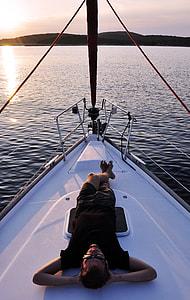 man laying on white boat