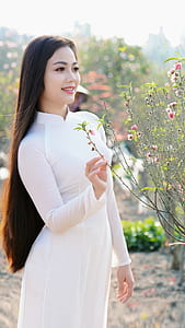woman wearing white long-sleeved dress near pink petaled flower plant