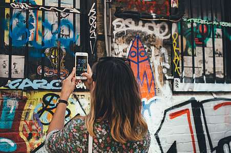 woman in black floral shirt holding silver iPhone 6 taking picture of graffiti