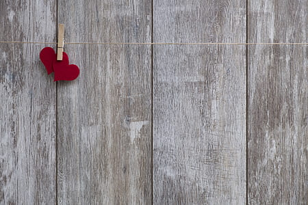 two red heart on string near grey wooden board
