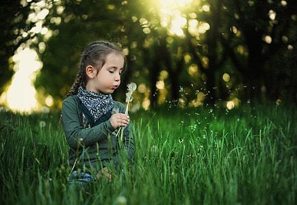 girl wearing green sweater blowing dandelion plant