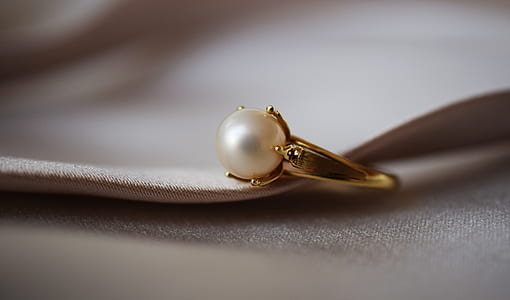 gold-colored ring with white pearl