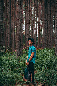 man in green western shirt and black denim jeans with black fedora hat standing in forest holding green and black backpack photoshoot