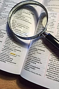 black magnifying glass on dictionary