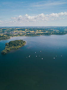 aerial photography of boats sailing near island during daytime