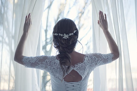 woman wearing white long-sleeved laced top holding white curtains