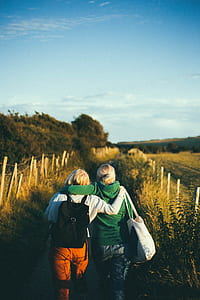 two woman walking on the road in between fields during daytime photography