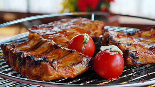 baby back ribs grilled on grilling tray with red tomatoes