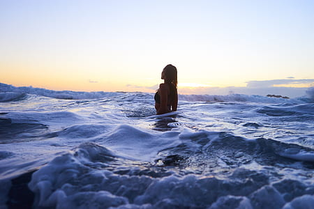 woman in ocean during daytime photography