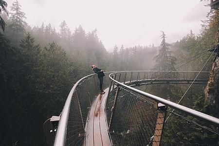 woman leaning on black metal hanging bridge