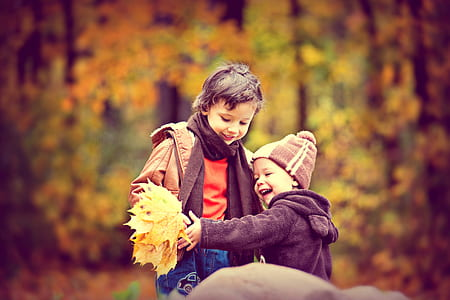 two children holding leaf