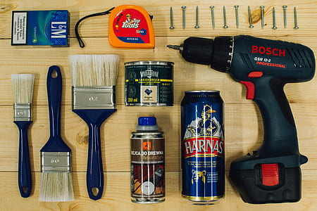 blue and black Bosch cordless power drill; orange and red tape measure; Harnas can; two assorted-label cans; L&M flip-top cigarette box; three blue wooden handled paint brushes