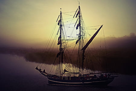 black galleon on body of water during sunset
