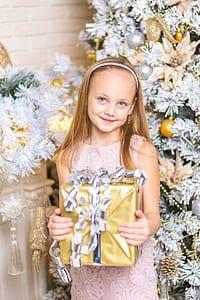 girl in pink lace sleeveless dress holding gold gift box in front of Christmas tree