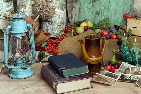 teal tubular lantern beside two books and brown pitcher on table
