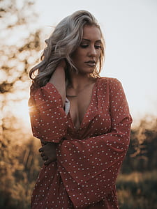 woman in red and white polka-dot plunging neckline long-sleeved dress