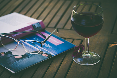 wine glass filled with liquor beside book and eyeglasses