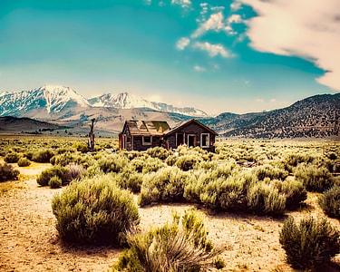 house standing on desert near mountains under cloudy sky