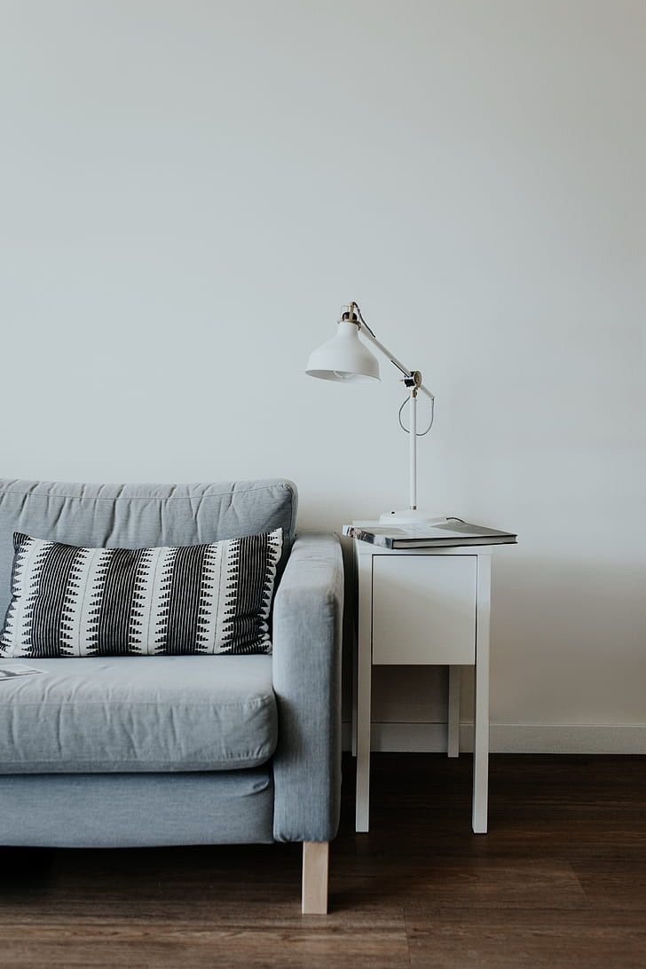 white task light on white side table beside blue sofa