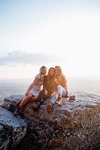 three women sitting on gray rock