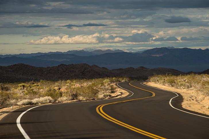 photo of asphalt road near desert