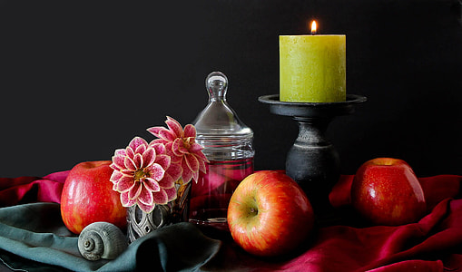 apple beside of black wooden candle holder with green votive candle on top table