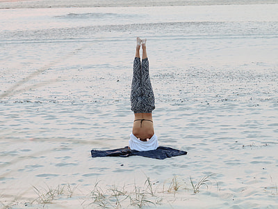 photo of person doing headstand in snow weather