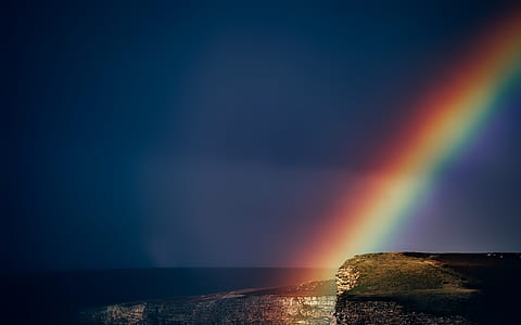 photo of cliff with rainbow