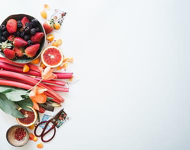 strawberry fruits beside orange petaled flower on white surface