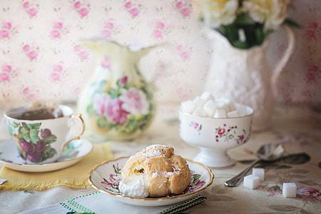 bread on floral saucer near tea set