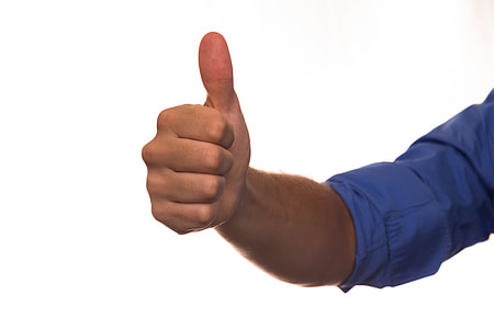 man wears blue dress shirt while doing thumbs up