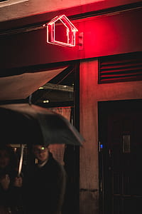 man and woman holding black umbrella near red neon light signage