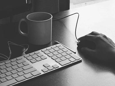 white Apple keyboard with white ceramic mug