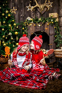two girls in red-white-and-black fair isle ear-flap hat and scarfs holding lollipops