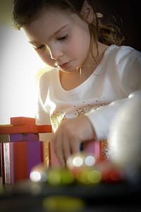 girl in white long-sleeved shirt playing toy